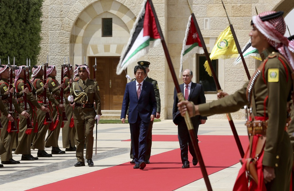 Japanese Prime Minister Shinzo Abe, centre left, arrives with Jordanian Prime Minister Hani Mulki, right, to meet with King Abdullah at the Royal Pala...