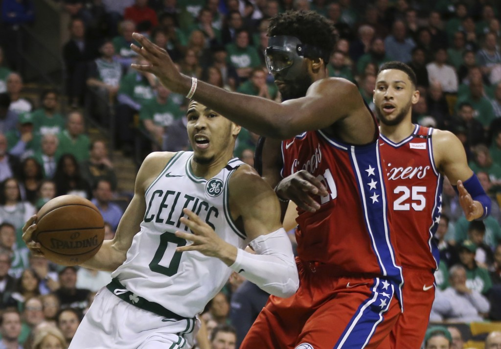 Boston Celtics forward Jayson Tatum (0) drives against Philadelphia 76ers center Joel Embiid (21) as 76ers guard Ben Simmons (25) looks on in the seco...