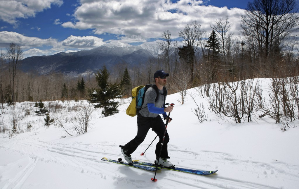 In this Saturday, April 21, 2018, photo, Drew Zimber skis through the Randolph Community Forest, north of the Mounts Madison and Adams, in background,...