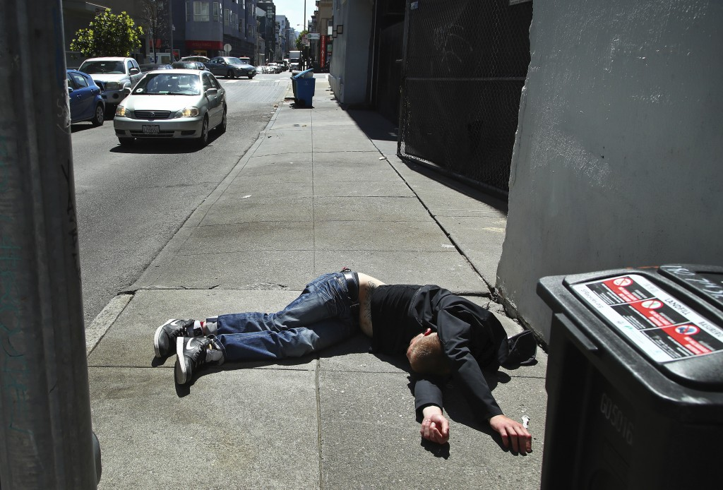 In this photo taken on Thursday, April 26, 2018, a man lies on the sidewalk beside a recyclable trash bin in San Francisco. San Francisco may have hit...