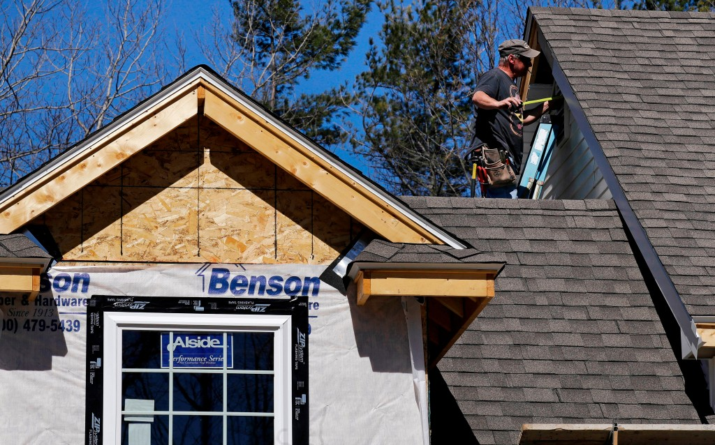 FILE- In this April 23, 2018, file photo, a worker installs vinyl siding on a new home in Auburn, N.H. On Tuesday, May 1, 2018, the Commerce Departmen...