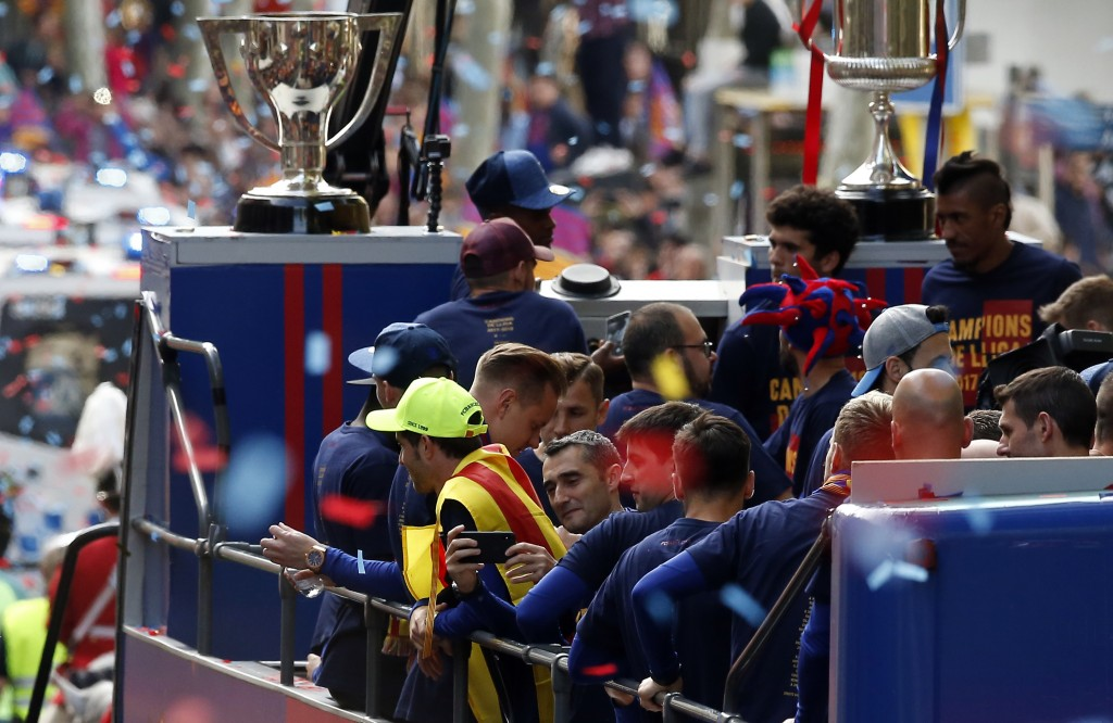Barcelona coach Ernesto Valverde, center, takes pictures from a bus with players celebrating during a street parade in Barcelona, Spain, Monday April ...