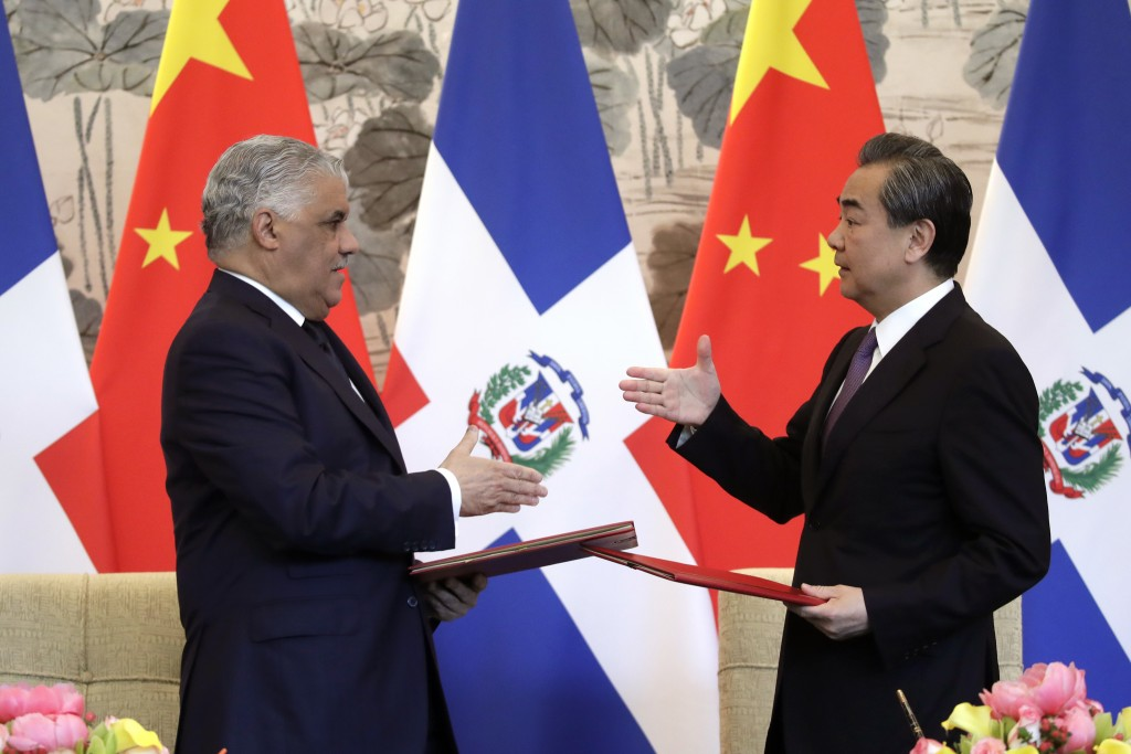 Dominican Foreign Minister Miguel Vargas, left, and Chinese Foreign Minister Wang Yi prepare to shake hands after they signed the joint communique at ...