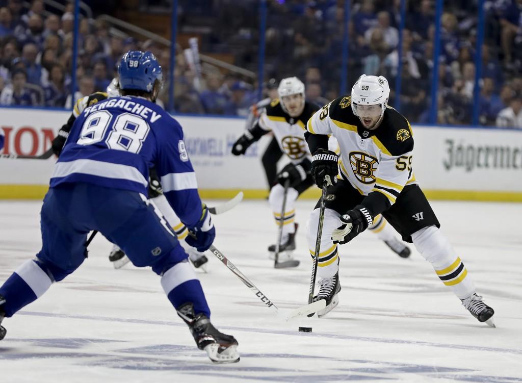 Boston Bruins center Tim Schaller, right, makes a move to get around Tampa Bay Lightning defenseman Mikhail Sergachev (98) during the first period of ...