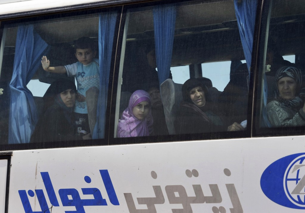 In this photo released by the Syrian official news agency SANA, released Syrian women and kids who were held with their families for years by al-Qaida...
