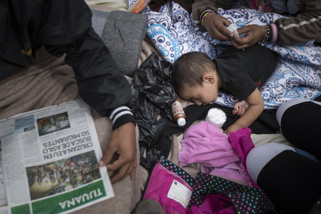 A two-year-old child from Honduras gets treatment for an ear infection after sleeping in the open in front of the El Chaparral port of entry, in Tijua...