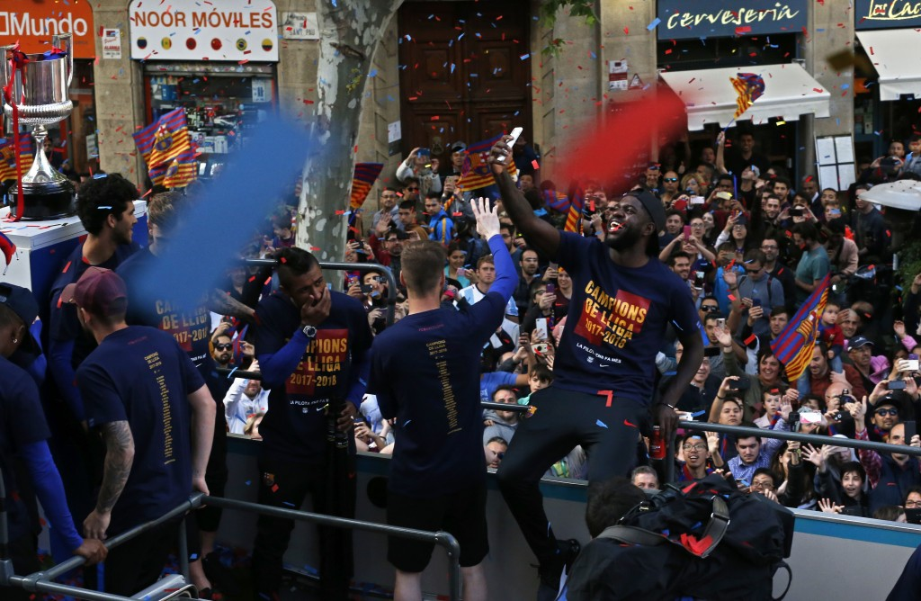 Barcelona's Samuel Umtiti takes a selfie from the bus carrying the team celebrating during a street parade in Barcelona, Spain, Monday April 30, 2018,...