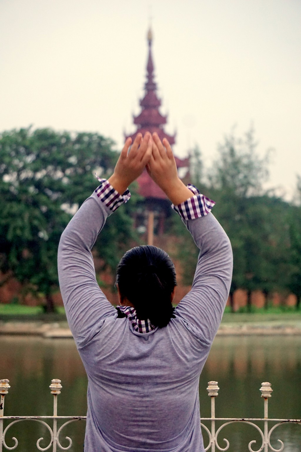This Nov. 3 2017, photo shows a woman doing morning exercises and paying reverence along the moat which surrounds the former royal palace in Mandalay....