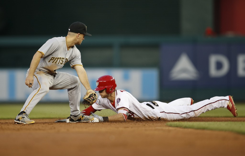 Washington Nationals' Trea Turner slides safely into second ahead of the tag by Pittsburgh Pirates second baseman Adam Frazier (26) after hitting a do...