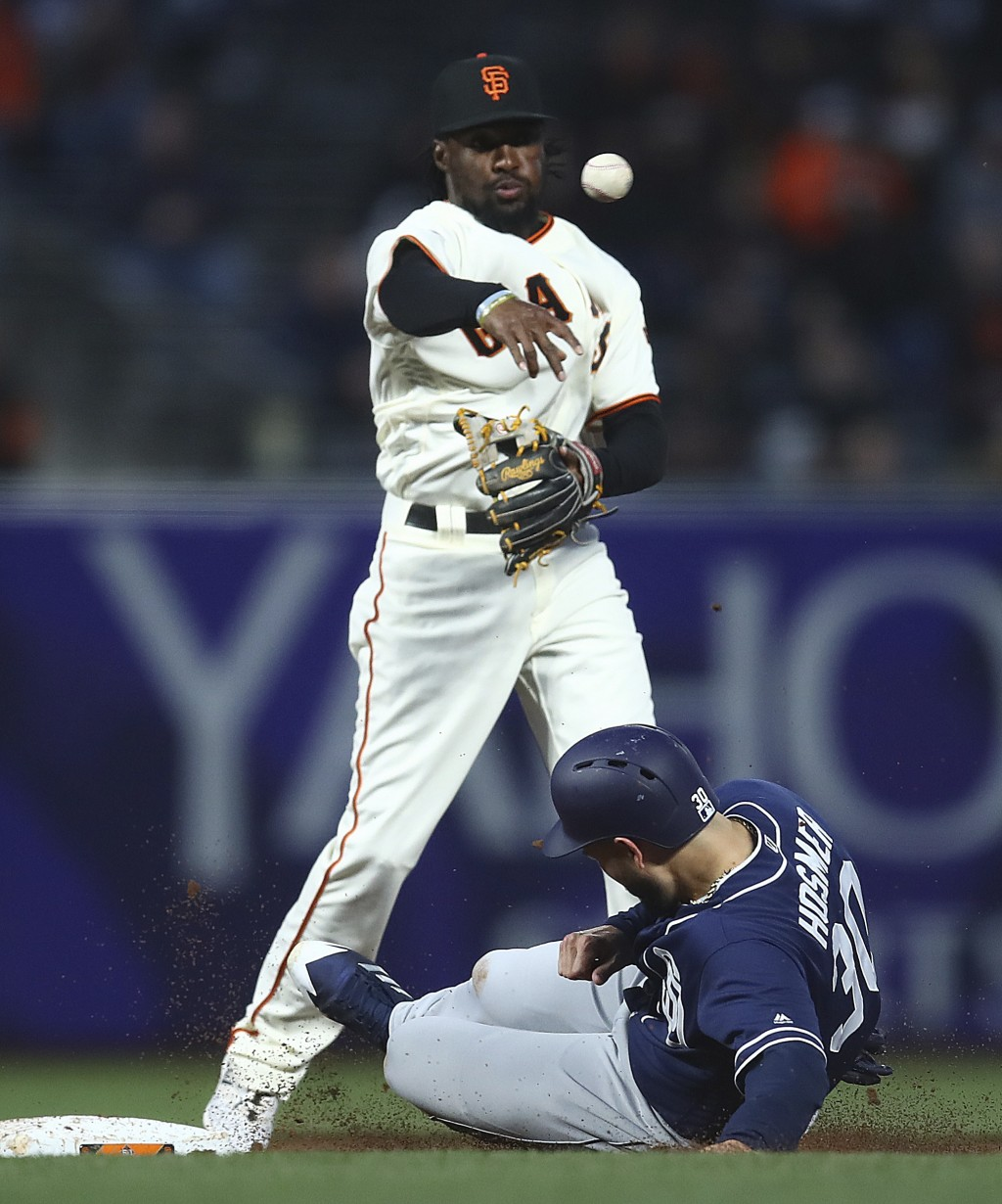 San Francisco Giants' Alen Hanson throws to first base over San Diego Padres' Eric Hosmer to complete a double play in the third inning of a baseball ...
