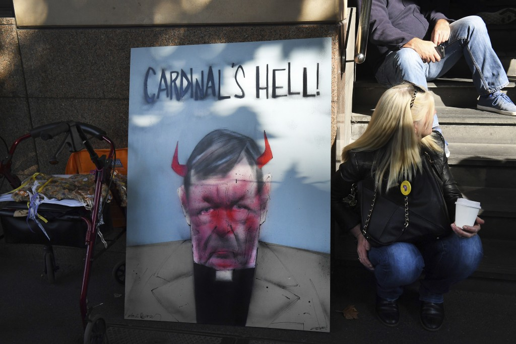 A demonstrator sits beside a placard carrying the image of Australian Cardinal Greorge Pell, outside the Melbourne Magistrate Court in Melbourne Tuesd...