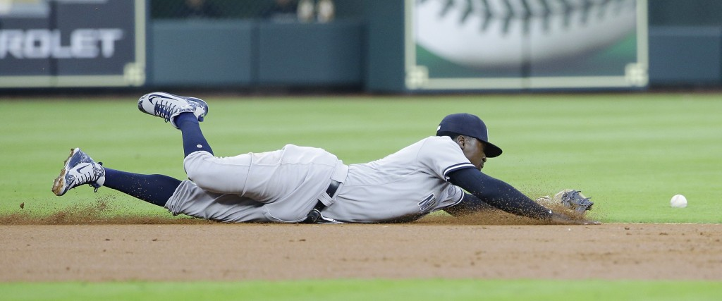 New York Yankees' shortstop Didi Gregorius (18) dives for the hit by Houston Astros' George Springer (4) during the first inning of a baseball game Mo...