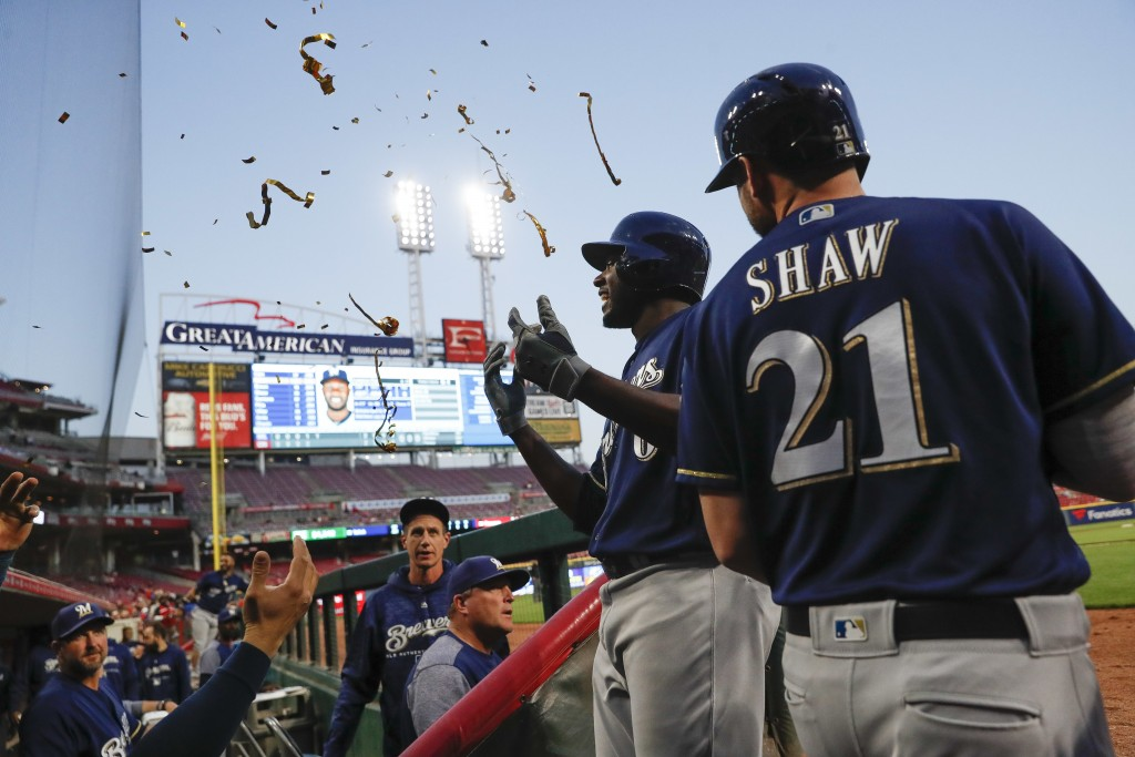 Milwaukee Brewers' Lorenzo Cain, center, is showered with confetti by teammates as he celebrates at the dugout after hitting a two-run home run off Ci...