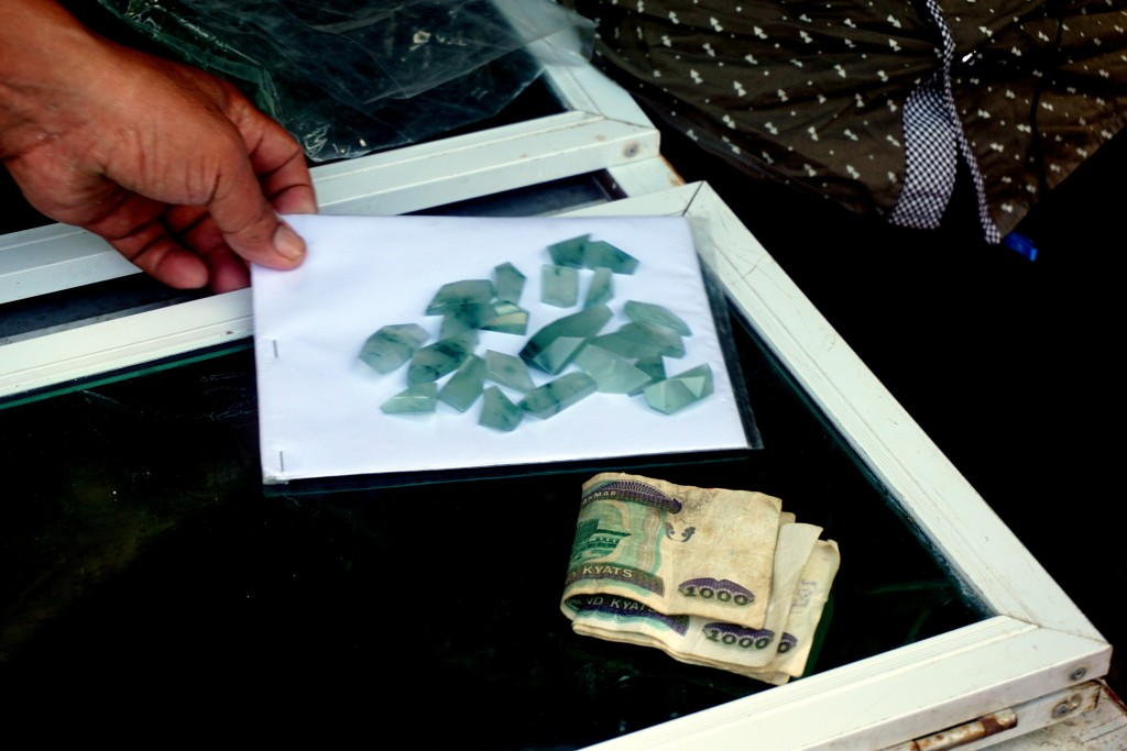 This Nov. 2, 2017, photo shows money exchanging hands for jade at the Mandalay jade market. The jade trade is dominated by the Chinese with large quan...