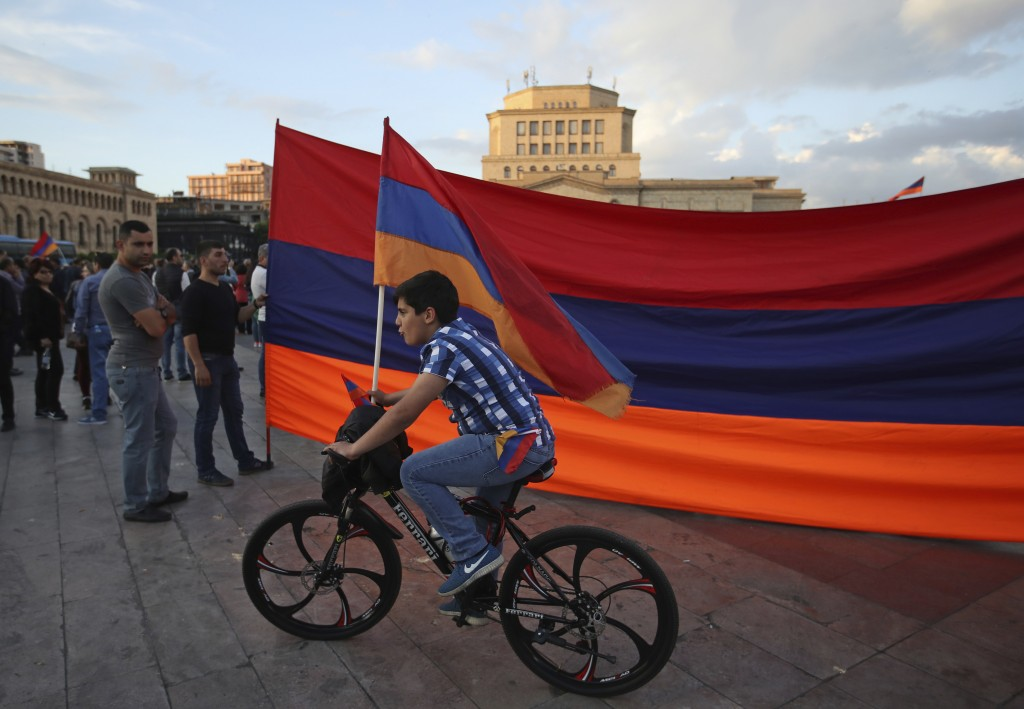Young boy rides his bike with supporters of the opposition lawmaker Nikol Pashinian who hold a large Armenian flag during a rally in Yerevan on Monday...