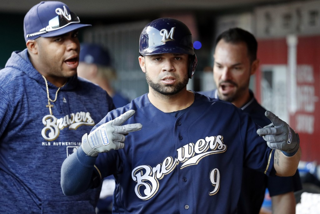 Milwaukee Brewers' Manny Pina (9) celebrates in the dugout after hitting a solo home run off Cincinnati Reds starting pitcher Brandon Finnegan in the ...