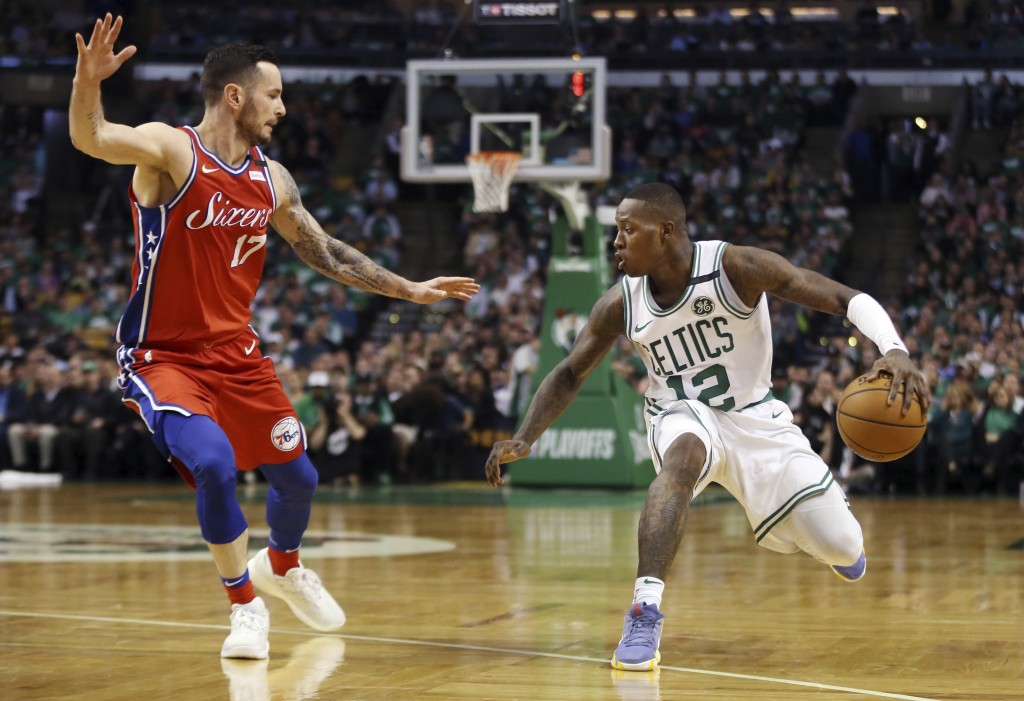 Boston Celtics guard Terry Rozier (12) makes a dribble move against Philadelphia 76ers guard JJ Redick (17) in the second half of Game 1 of an NBA bas...