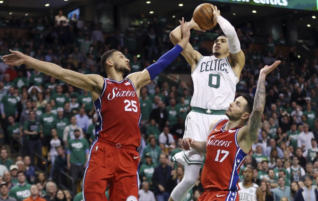 Boston Celtics forward Jayson Tatum (0) shoots against Philadelphia 76ers guard Ben Simmons (25) and guard JJ Redick (17) in the second half of Game 1...