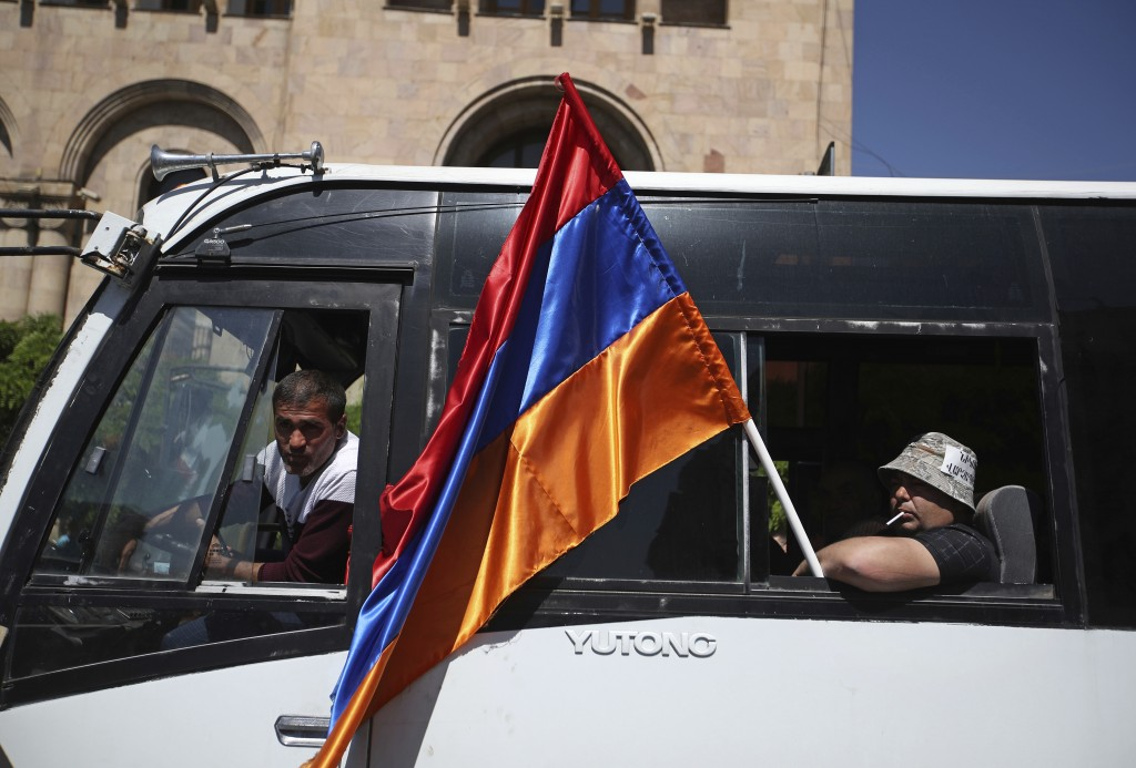 A supporter of the opposition lawmaker Nikol Pashinian sits in a bus holding a national flag during a rally at the Republic square in Yerevan on Tuesd...
