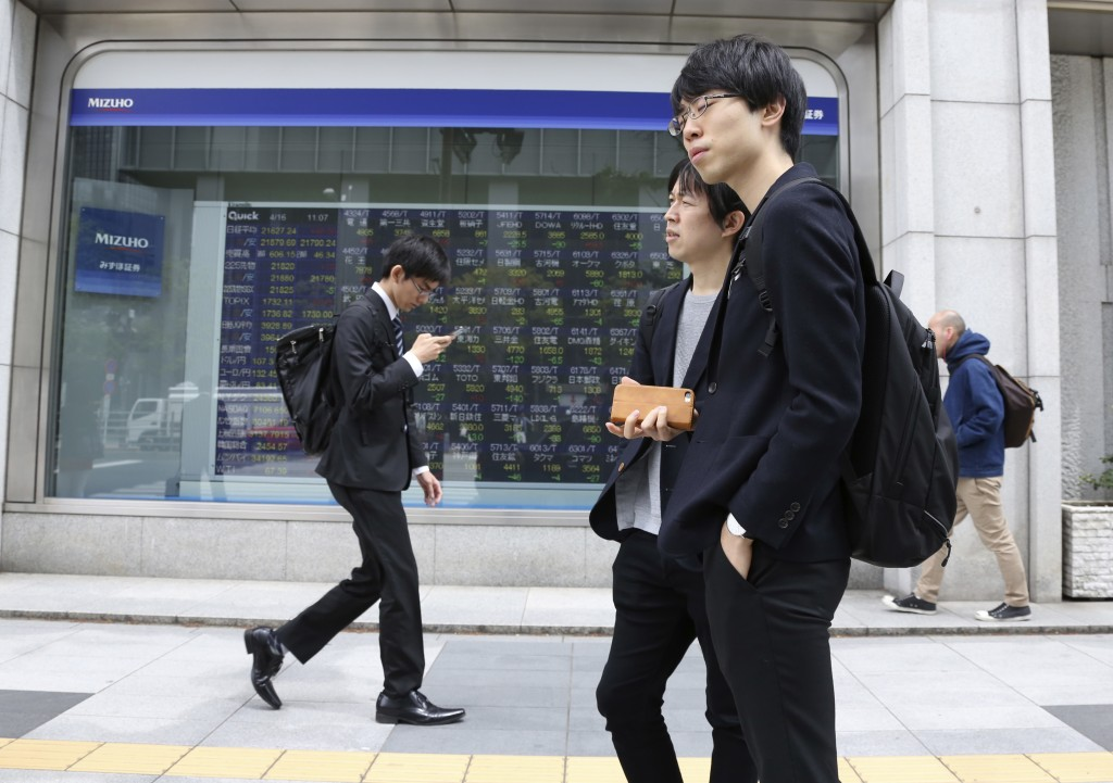 In this April 16, 2018, file photo, people walk by an electronic stock board of a securities firm in Tokyo. Tokyo stocks were marginally higher Tuesda...