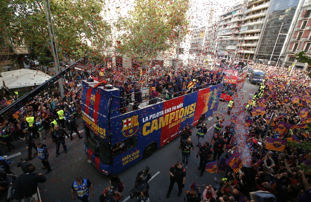 Barcelona players on a bus celebrate during a street parade in Barcelona, Spain, Monday April 30, 2018, after winning the Spanish La Liga soccer title...