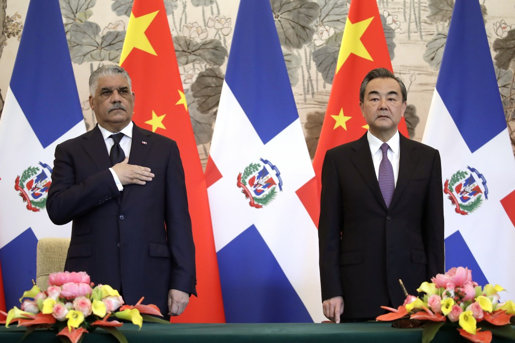 Dominican Foreign Minister Miguel Vargas, left, and Chinese Foreign Minister Wang Yi stand as they listen to the national anthems of their countries a...