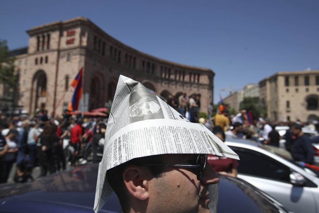 A supporter of the opposition lawmaker Nikol Pashinian, wears a makeshift hat from a newspaper with his image on during a rally at the Republic square...