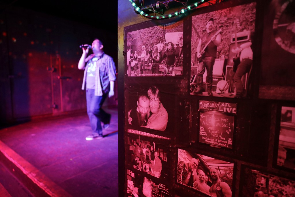 In this Monday, April 30, 2018, photo, photographs decorate a wall next to a stage during karaoke night at The SF Eagle, a historic gay bar, in San Fr...