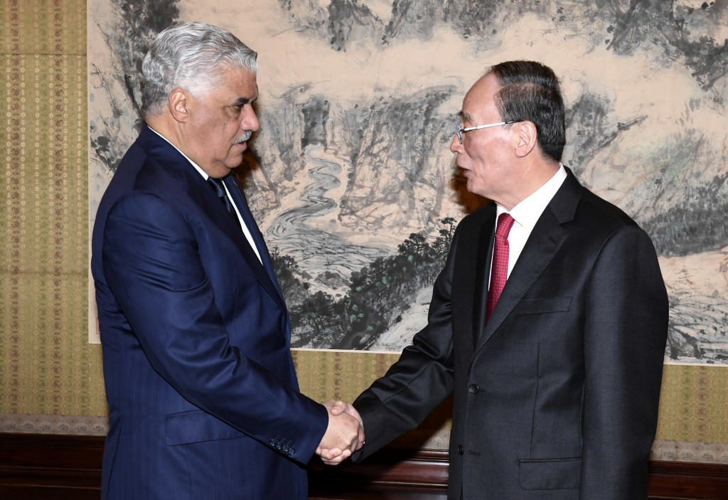 Chinese Vice President Wang Qishan, right, shakes hands with Dominican Republic's Foreign Minister Miguel Vargas during a meeting at the Zhongnanhai L...