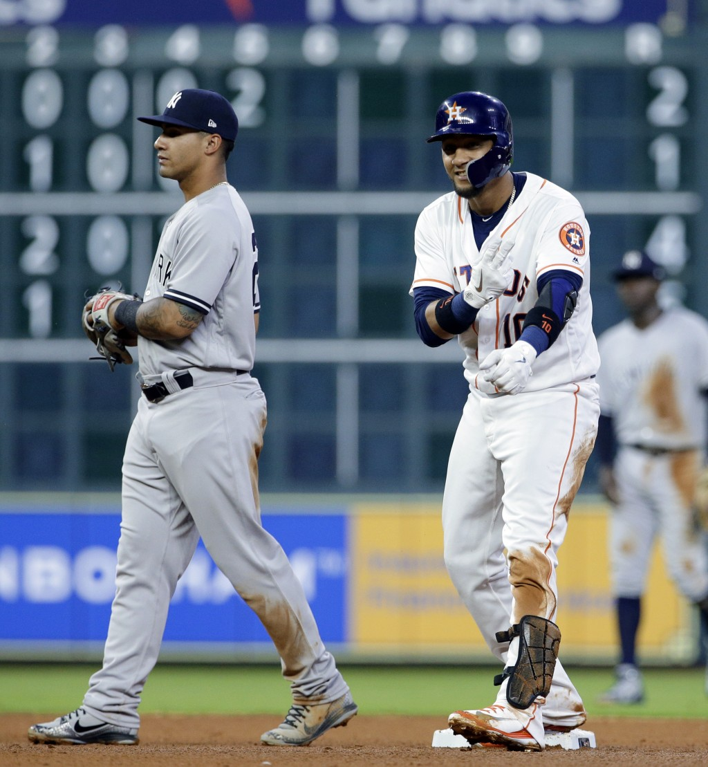 Houston Astros' Yuli Gurriel (10) reacts to his double nest to New York Yankees' second baseman Gleyber Torres (25), driving in Jose Altuve to score d...