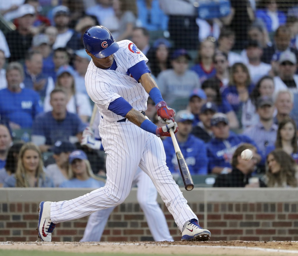 Chicago Cubs' Addison Russell hits an RBI single off Colorado Rockies starting pitcher Kyle Freeland during the second inning of a baseball game Monda...