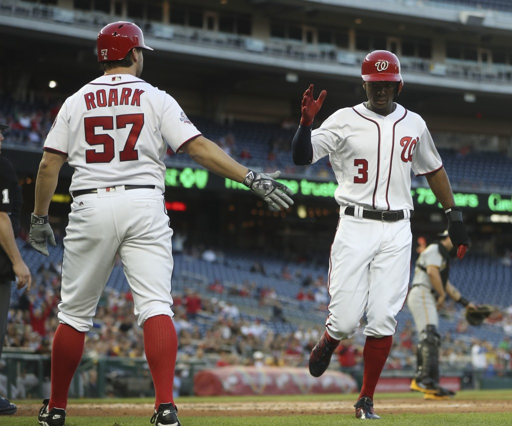 Washington Nationals' Michael Taylor (3) is greeted by Tanner Roark (57) after scoring on a single by teammate Wilmer Difo during the second inning of...