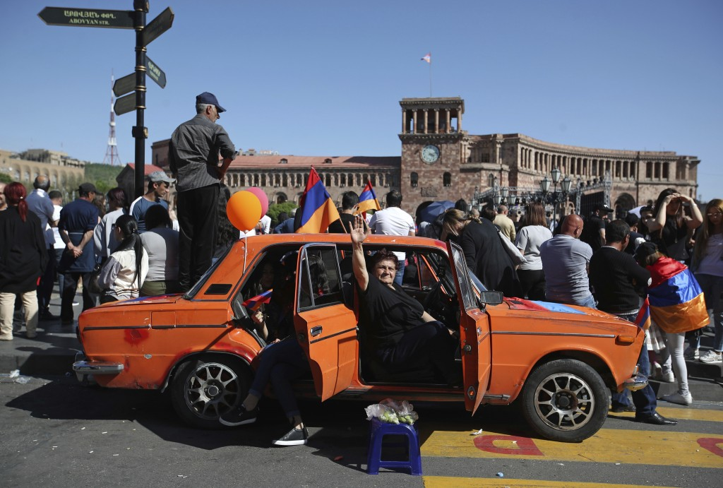 A woman waves from a car as supporters of the opposition lawmaker Nikol Pashinian hold a rally in the Republic square in Yerevan on Tuesday, May 1, 20...
