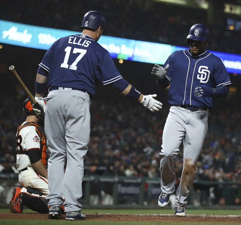 San Diego Padres' Franchy Cordero, right, is congratulated by A.J. Ellis (17) after scoring against the San Francisco Giants the fourth inning of a ba...