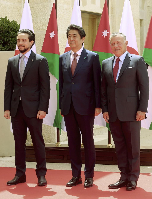 King Abdullah II of Jordan, right, and Crown Prince Hussein, left, receive Japanese Prime Minister Shinzo Abe at the Husseiniya palace in Amman, Jorda...