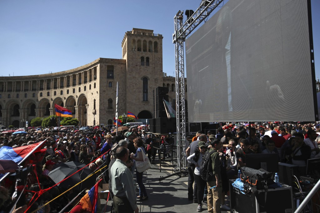 Supporters of the opposition lawmaker Nikol Pashinian, look at a large screen of him speaking in parliament during a rally at the Republic square in Y...