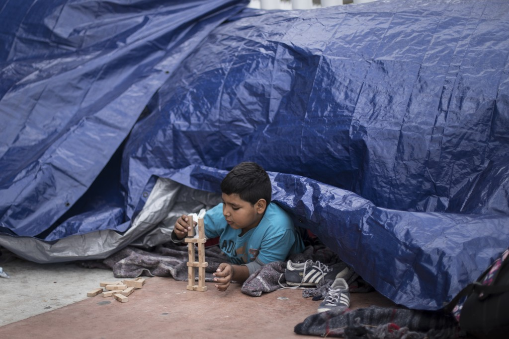 A migrant child from El Salvador plays under a tarpaulin at the El Chaparral port of Entry, in Tijuana, Mexico, Monday, April 30, 2018. bout 200 peopl...