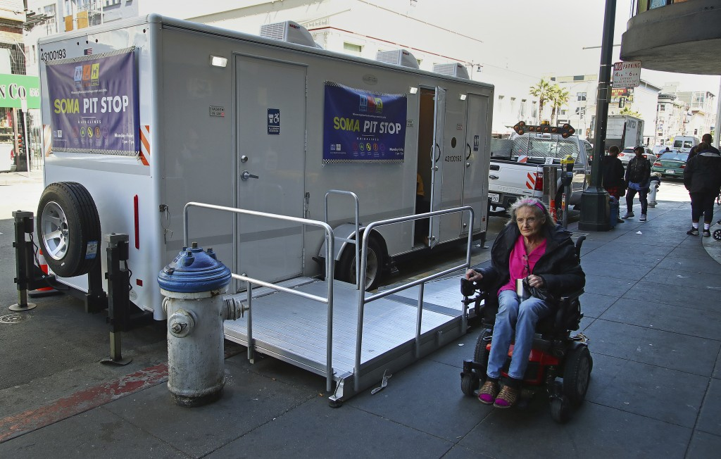 In this photo taken on Thursday, April 26, 2018, a woman in a wheelchair passes a Pit Stop in San Francisco. The Pit Stop program provides public toil...