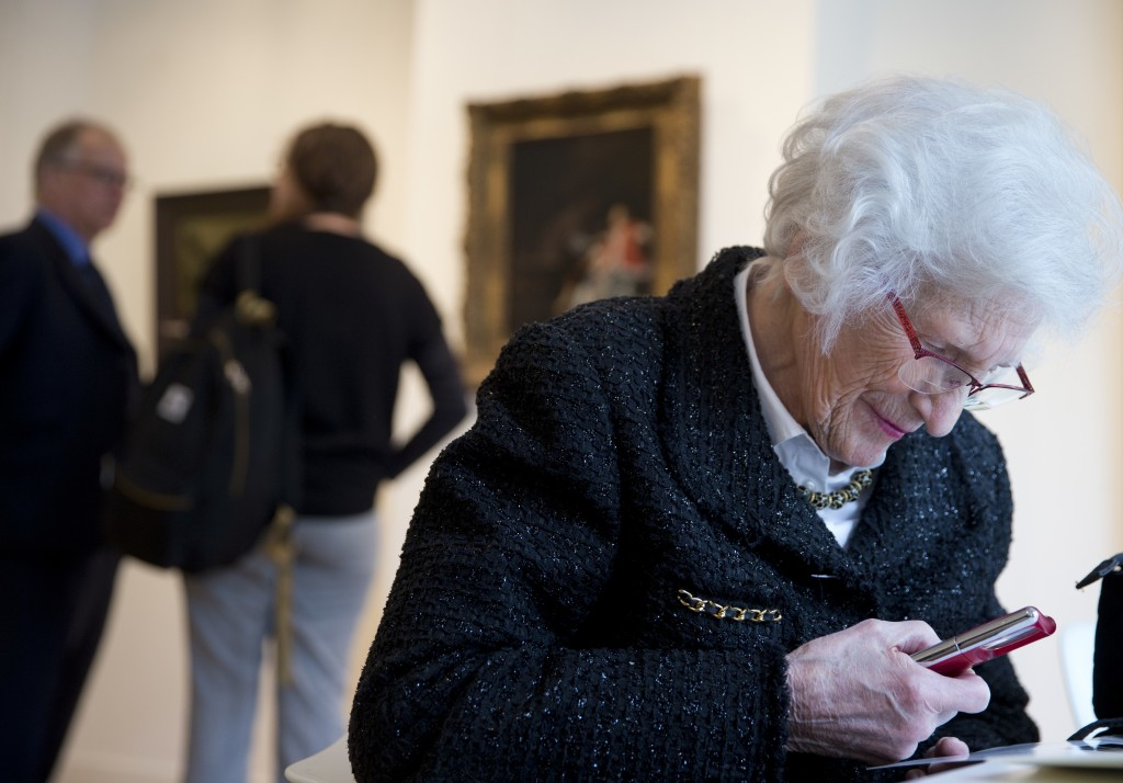 """Ninety-seven-year-old Charlotte Bischoff van Heemskerck reads the press release on the recovery of the painting """"The Oyster Meal"""" by Jacob Ochtervelt ..."""