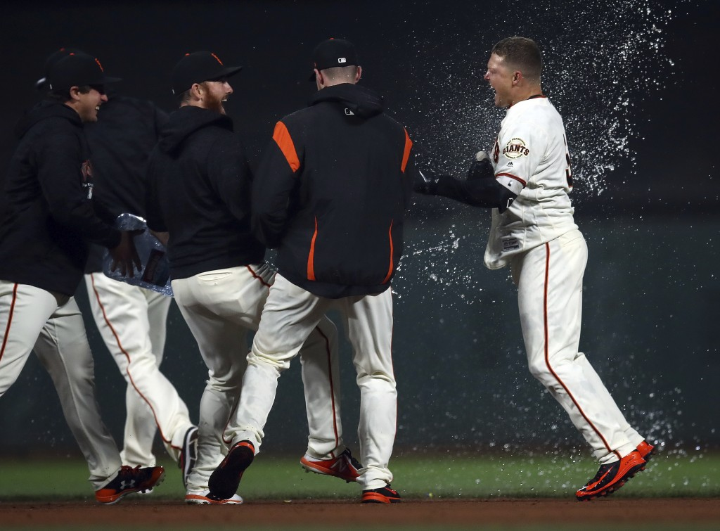 San Francisco Giants' Nick Hundley, right, celebrates after making the game-winning hit against the San Diego Padres in the ninth inning of a baseball...