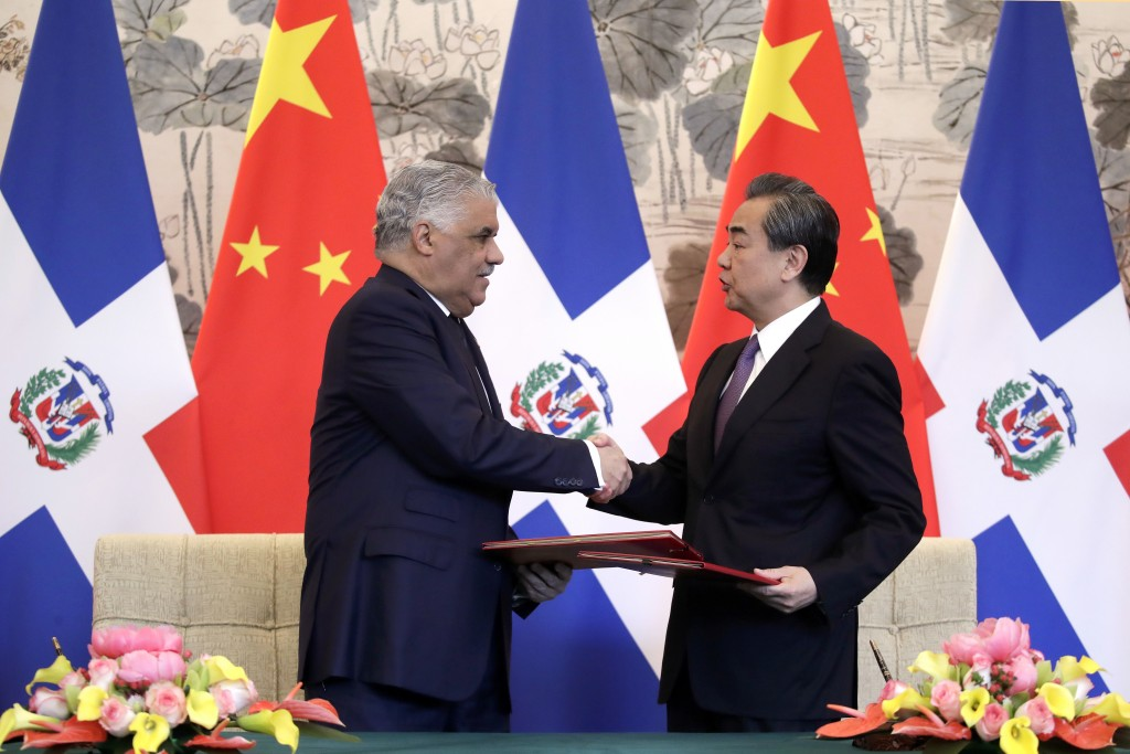 Dominican Foreign Minister Miguel Vargas, left, and Chinese Foreign Minister Wang Yi shake hands after they signed the joint communique at the Diaoyut...