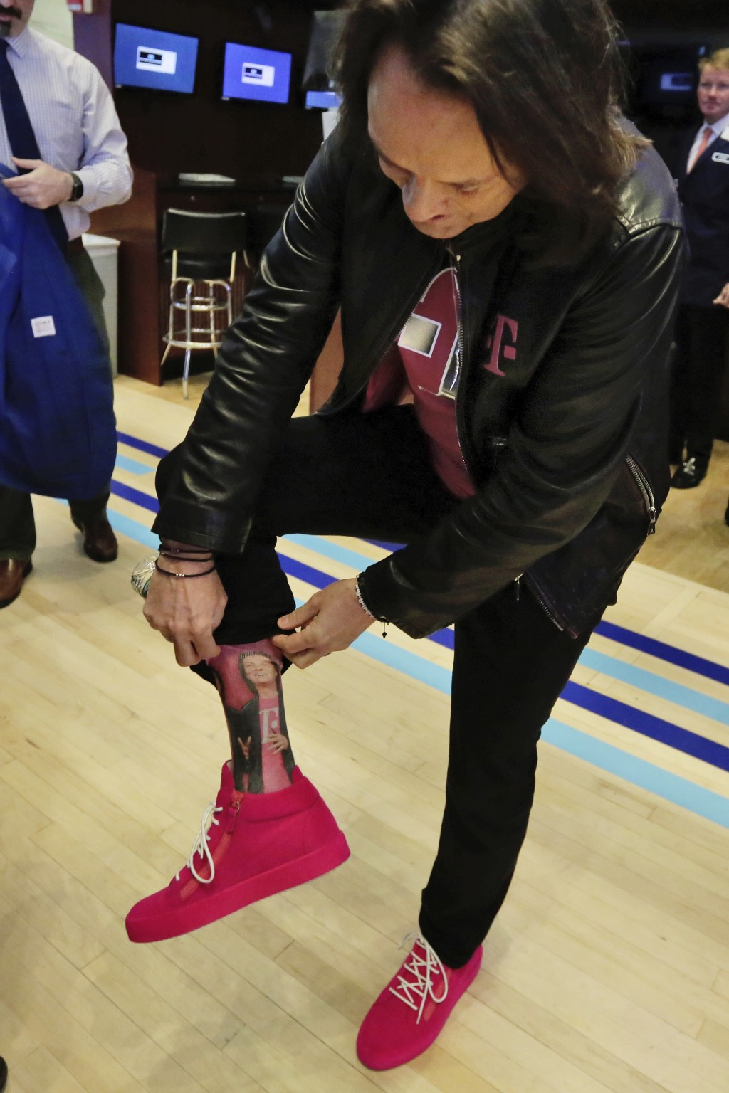 T-Mobile CEO John Legere shows off his personalized socks on the floor of the New York Stock Exchange, Monday, April 30, 2018. To gain approval for th...