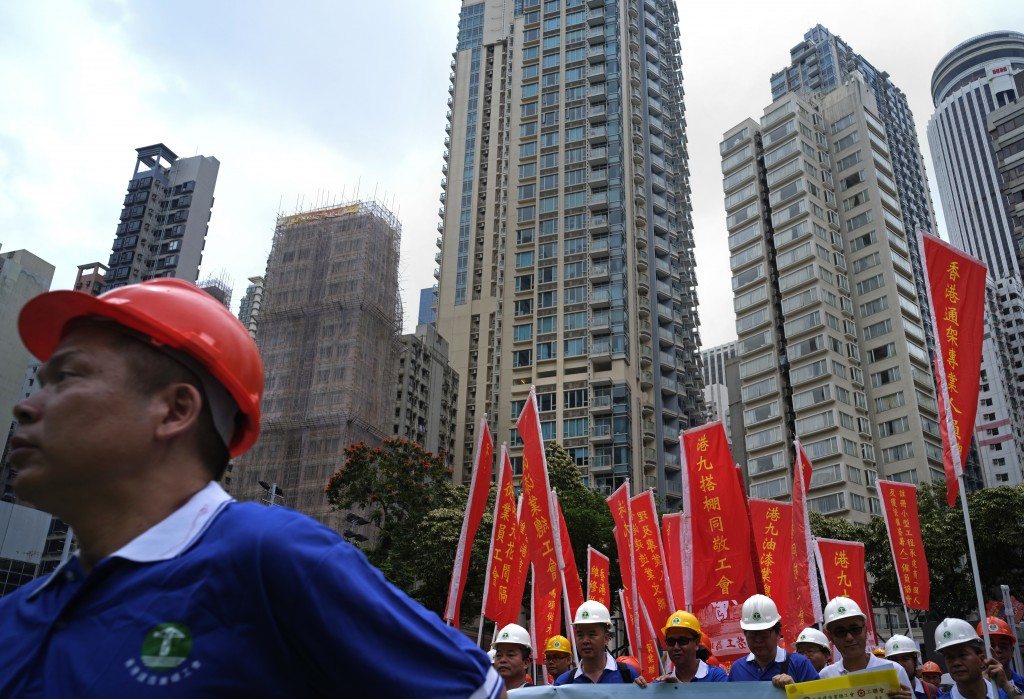 Workers wear safety hats and hold banners during a march to mark May Day in Hong Kong Tuesday, May 1, 2018. Hundreds of Hong Kong workers from various...