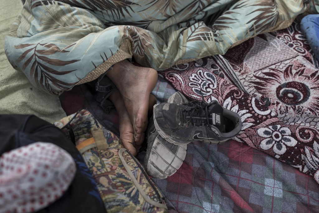 A migrant who traveled with the annual caravan of Central American migrants, rest where the group set up camp to wait for access to request asylum in ...