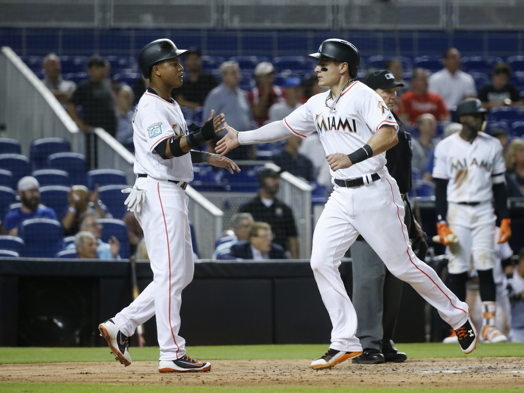 Miami Marlins' Starlin Castro, left, and Derek Dietrich congratulate each other after they scored on a double by Brian Anderson during the third innin...