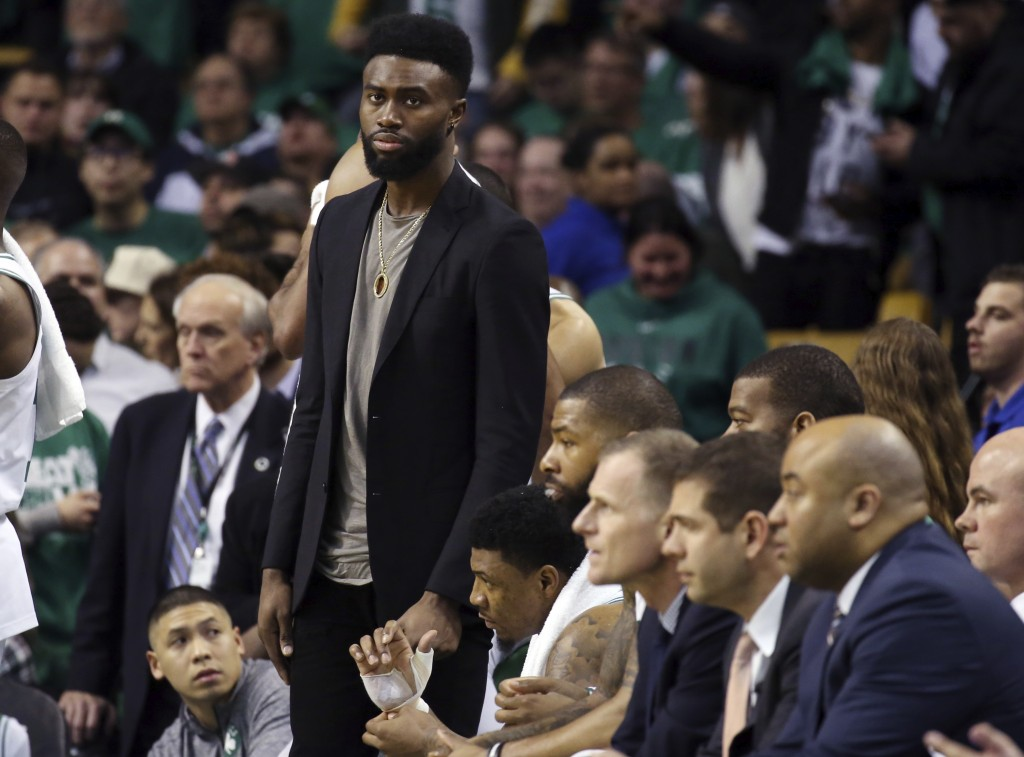 Injured Boston Celtics guard Jaylen Brown stands at the bench in street clothes as he watches the second half against the Philadelphia 76ers in Game 1...