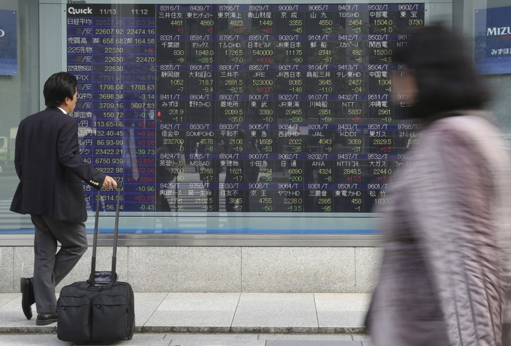 In this Nov. 13, 2017, photo, a man looks at an electronic stock board of a securities firm in Tokyo. Tokyo stocks were marginally higher Tuesday, May...
