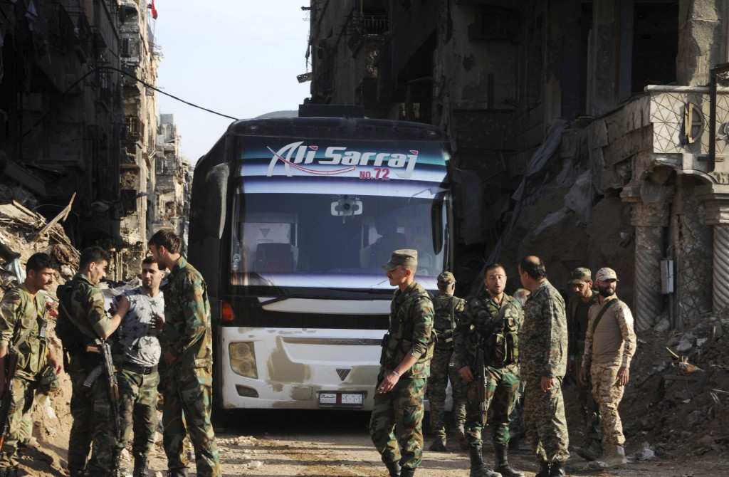 In this photo released on Monday, April 30, 2018 by the Syrian official news agency SANA, Syrian government forces gather in front of a bus carrying a...