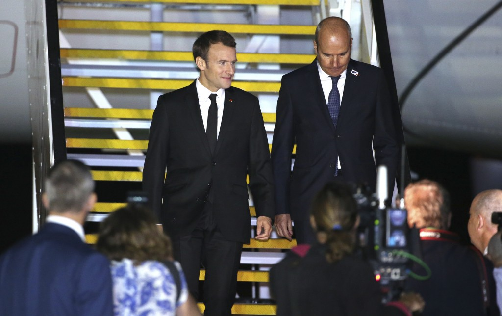 French President Emmanuel Macron, top left, walks down the stairs with France's Ambassador to Australia, Christophe Penot, as he arrives in Sydney, Tu...