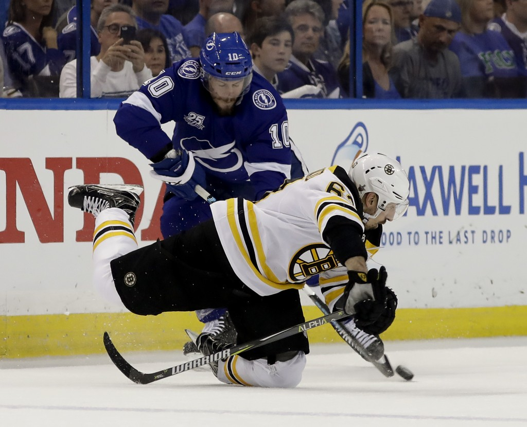 Boston Bruins left wing Brad Marchand, lower right, falls after getting tangle up with Tampa Bay Lightning center J.T. Miller (10) during the first pe...